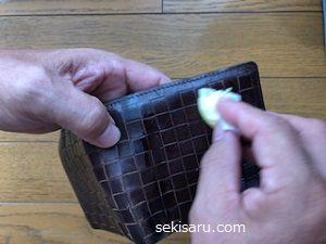 コットンで財布を拭く