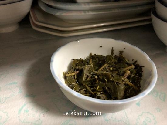 炒った緑茶の葉を小皿に盛って食器棚の中に置く