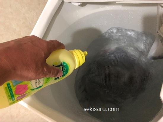 洗濯機にリュックと洗剤を入れる