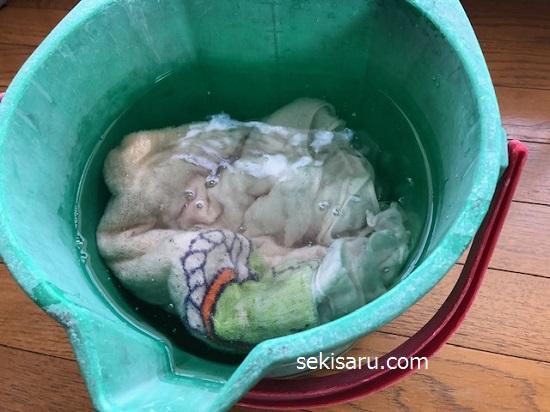重曹を加えたお湯の中にバスタオルを浸けこむ