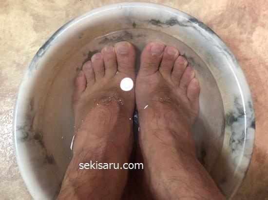 重曹を溶かしたぬるま湯が入っている洗面器の中に足を入れる