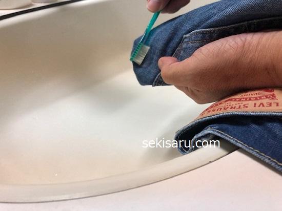 歯ブラシでジーンズに酸素系漂白剤を塗る