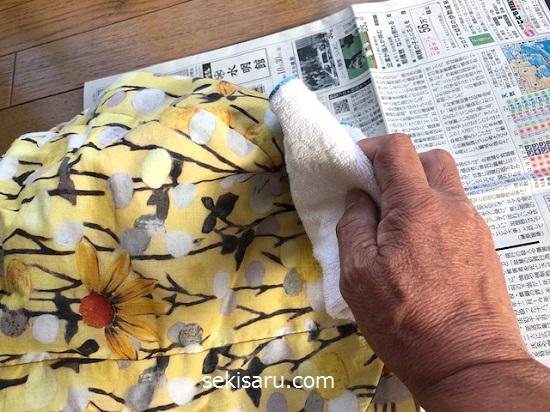 アルコール消毒液がついたタオルでバッグに生えたカビの箇所を拭く